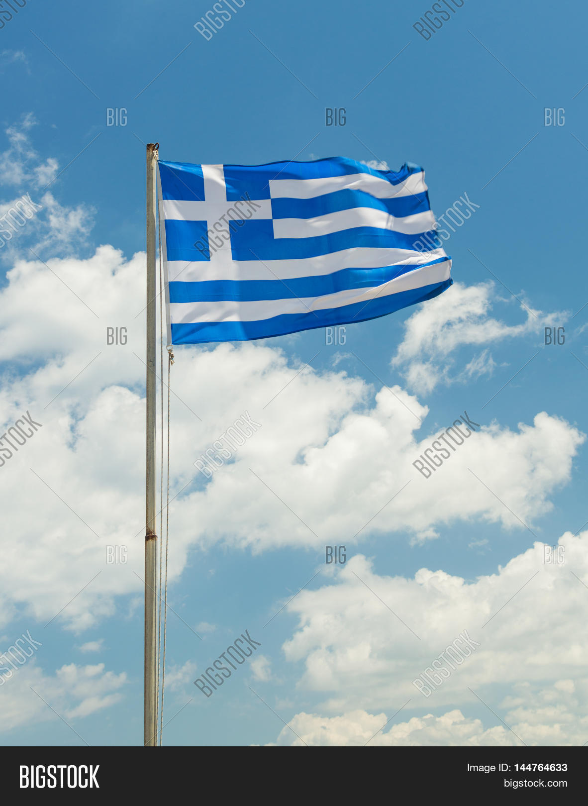 National flag of Greece in the wind. Blue sky with white clouds on background.