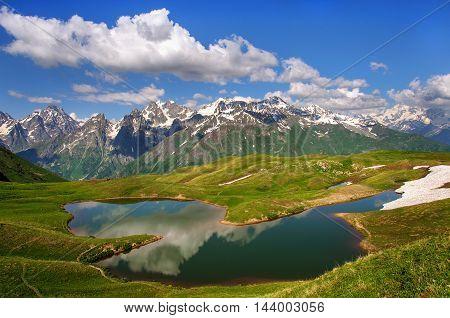Reflection of snow-capped peaks of the main Caucasian ridge into the lake koruldi. Georgia, Svaneti