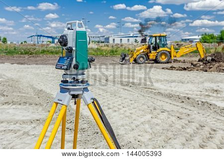 Surveyor engineer is measuring level on construction site. Surveyors ensure precise measurements before undertaking large construction projects. poster