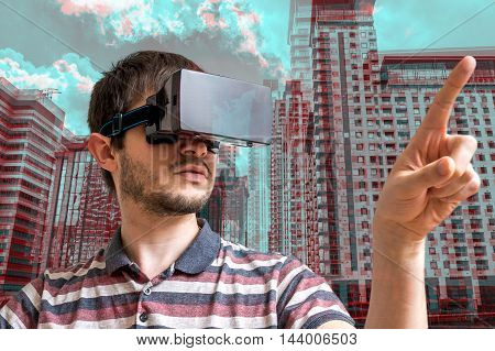 Young Man Is Wearing Virtual Reality Headset. 3D Simulation Of C