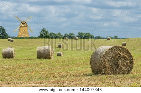 countryside with hilly field and rolls of haystack. Focus is on the nearest roll