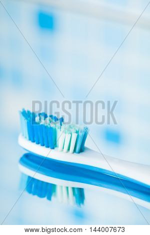 toothbrush on blue tile background with mirror reflection
