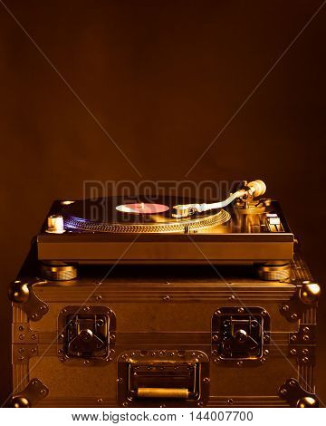 professional dj turntable on flight case, dark background, golden tone