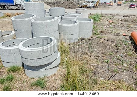 New concrete prefabricated pipes for manhole or drainage stacked at building site.