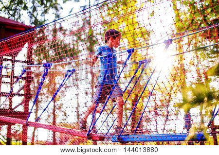 children's safety on playground. boy plays in the playground shielded with a protective safety net. blurred background, blurred motion due to the concept