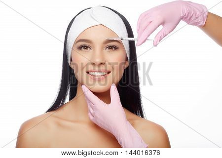 Beautiful woman getting lifting injection in forehead. Close-up woman hyaluronic acid injection. Injections of skin rejuvenation. Cosmetic procedures, injections, hyaluronic acid. poster