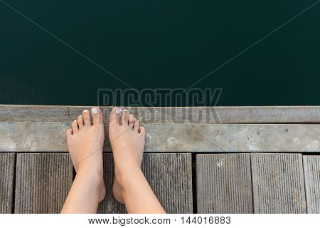 Female Feet on Wooden Deck by the Sea. Bare Woman Feet with White Painted Toenails on Wooden Background.