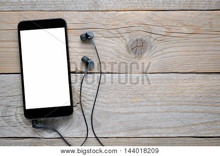 Smartphone with headphones on old wooden table