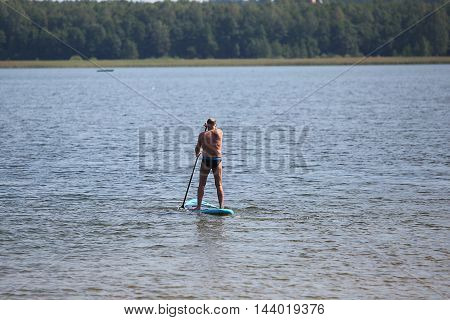 Senior Male Exercising On Sup Board