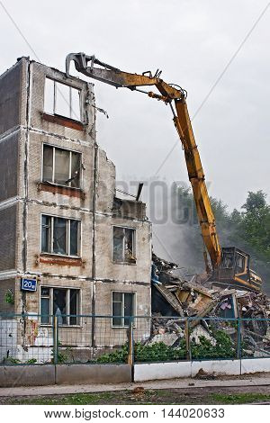 Excavator destroys the old soviet apartment house