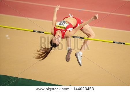 LINZ, AUSTRIA - FEBRUARY 22, 2015: Ekaterina Kuntsevich (#119 Austria) competes in the women's high jump event in an indoor track and field event.