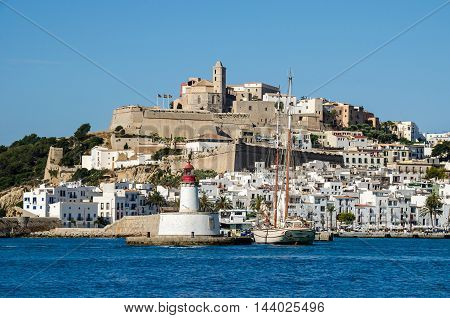 Ibiza Spain - June 3 2016: View of the Dalt Vila (Upper Town) of Eivissa (Ibiza Town) with its cathedral lighthouse and an old sailboat