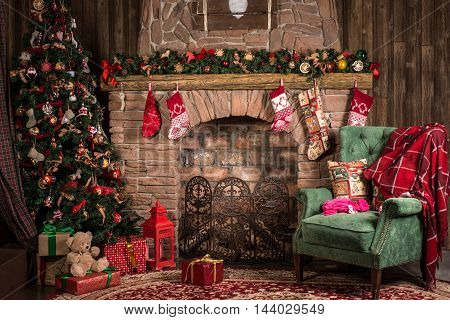 Christmas and New Year decoration: a fireplace, Christmas tree and green chair with red plaid