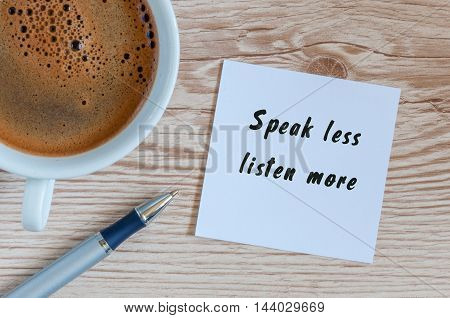 Speak Less Listen More phrase written on paper and cup of brasilian coffee on wooden background.