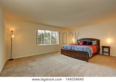 Large Beige Bedroom Interior. Wooden Bed With Drawers.