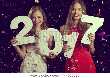 Two beautiful women having fun at New Year's Eve party holding cardboard numbers 2017