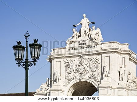 """Detail of the Rua Augusta Triumphal Arch depicting the female allegory of Victory rewarding Valor and Genius in Lisbon Portugal Translation: """"To the virtues of our ancestors who taught us everything"""" paid for at public expense poster"""