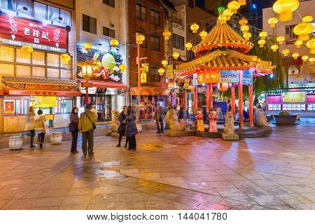 KOBE, JAPAN - NOVEMBER 26, 2012: Visitors enjoy Kobe's Chinatown in the evening. It is one of three designated Chinatowns in Japan.