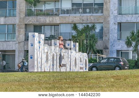 MONTEVIDEO, URUGUAY, DECEMBER - 2015 - Attractive young woman posing for photo at landmark place in which is located the Montevideo letters.
