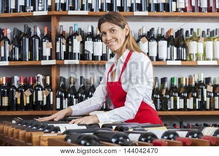 Saleswoman Arranging Wine Bottles In Rack