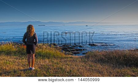 Young woman with long hairs standing on the beach