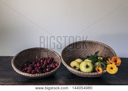 Cheeries apples and flowers in two round baskets