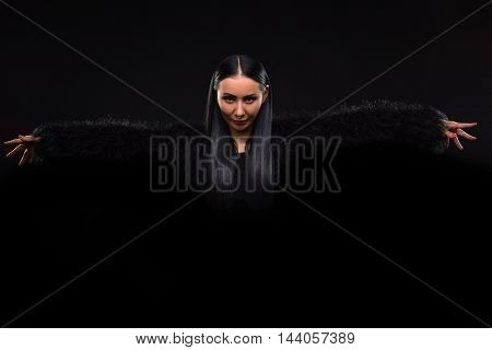 Beautiful brunette lady looking like watch or magician over dark background. Lady in black clothes.