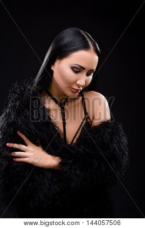 Beautiful brunette in black dress with perfect decollete over black background. Elegant and gorgeous vampire in studio.