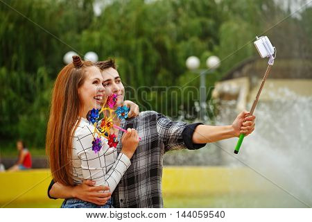Enamoured teenagers do selfie. Girlfriend and boyfriend strolling in a city park. Boy holding a selfie stick with a smartphone and hugs girl. Girl holds a the pinwheel. First love. He falls in love. Date.