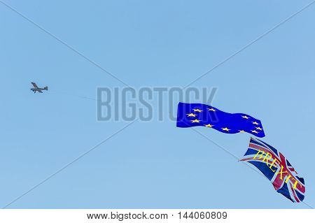 Banner towing small engine aircraft towing banners for advertising. Here the flag of Great Britain with text Proposed referendum on United Kingdom membership of the European Union.