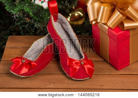 Close-up of red house slippers lying near New Year and Christmas presents and gifts. Red house slippers are nice idea for present or gift.