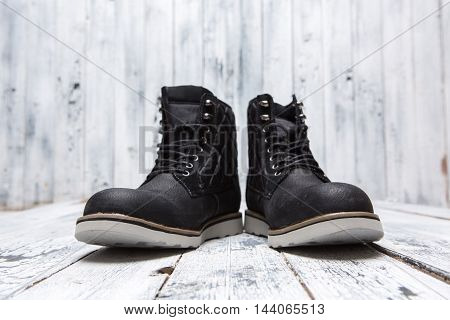 Footwear concept. Men's winter boots of black colour isolated on white wooden background. A pair of boots represented one near another.