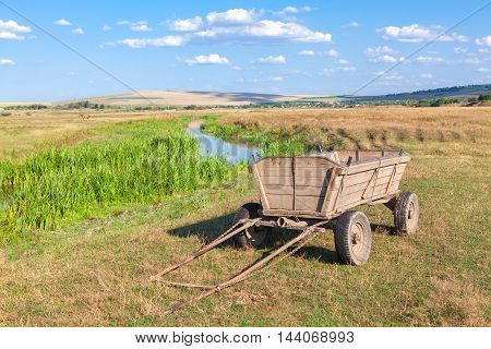 wooden cart without horses on the riverside