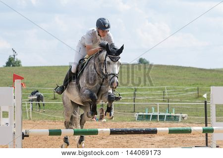 SVEBOHOV CZECH REPUBLIC - AUG 20: Closeup front view of horseman jumping a roan horse at