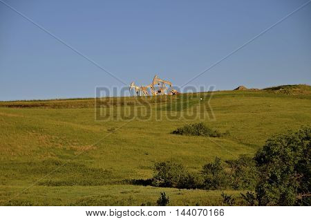 The tops of oil pumps in the western North Dakota oil fields can be seen in the skyline
