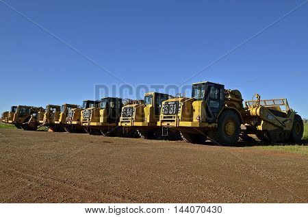 WATFORD CITY, NORTH DAKOTA, June 24, 2016: Founded in 1925, this row of tractors are  from Caterpillar Inc., an American corporation which designs, develops, engineers, manufactures, markets and sells machinery, engines, financial products and insurance