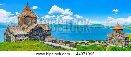 Panorama of the churches of Sevanavank Monastery with the medieval cemetery between them and the wide Sevan Lake on the background Armenia.