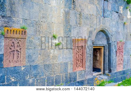 The frontage wall of Hayravank Monastery decorated with the red khachkars built in it Armenia.