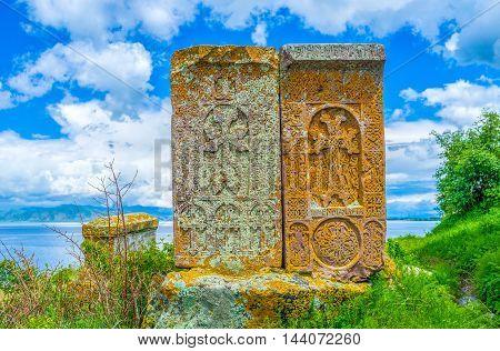 Two medieval tombstones named in Armenia the khachkars among the greenery on the bank of Sevan Lake Hayravank Armenia.