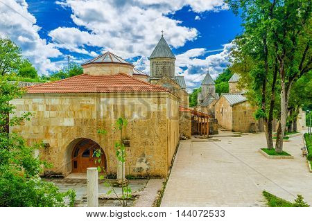 The renovated buildings of Haghartsin Monastery - Refectory and three churches on the background Armenia.