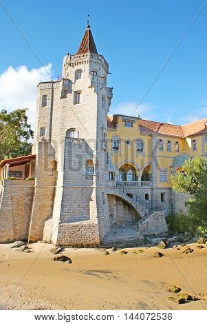 The medieval stone tower of Palace of Condes de Castro Guimaraes located on the sand shore of a small bay Cascais Portugal.