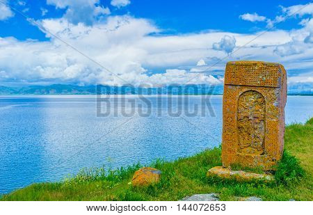 The orange khachkar covered with lichen located on the bank of Sevan Lake on cemetery of Hayravank Monastery Armenia.