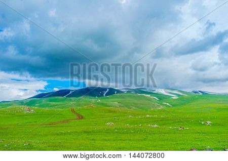 The cloudy weather in highlands with the small snowfields on the mountain top Gegharkunik Province Armenia.