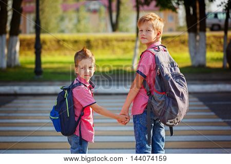 Portrait two adorable boys with backpack near pedestrian crossing the street