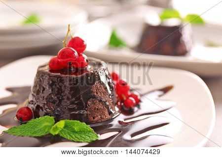 Chocolate fondant cake with fresh red currant and mint on the plate, closeup