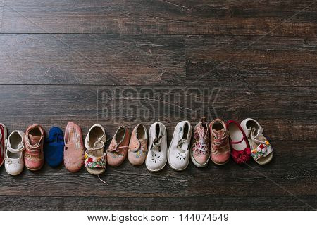 Old worn baby (child kid) shoes on the floor. sandals boots slippers.baby feet (legs foot).