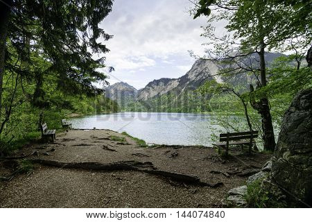 Alpine lake Schwansee with benches for rest and mountains on the background