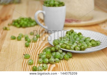 Plate with gooseberries on wooden background