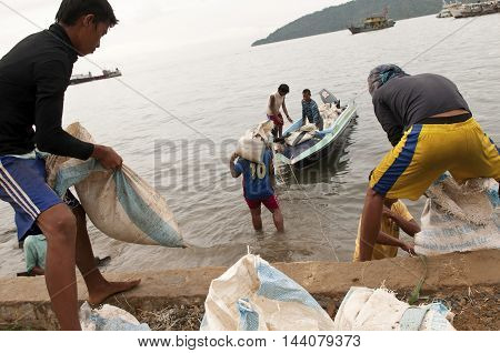 KOTA KINABALU, BORNEO, MALAYSIA - Dec 24 2011: Workers load a boat at a port.