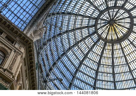 Multiple glass windows as part of domed ceiling. Horizontal format with metallic and glass dome structure detail under blue sky.